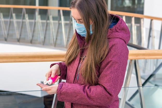 Conceito de prevenção de doenças virais. jovem mulher em uma máscara protetora médica usando gel desinfetante para as mãos como proteção contra vírus e bactérias no shopping. prevenção de coronavírus.
