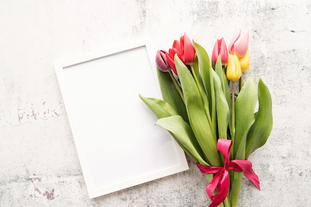 Conceito de primavera. buquê de tulipa colorida e quadro em branco sobre fundo branco com espaço de cópia