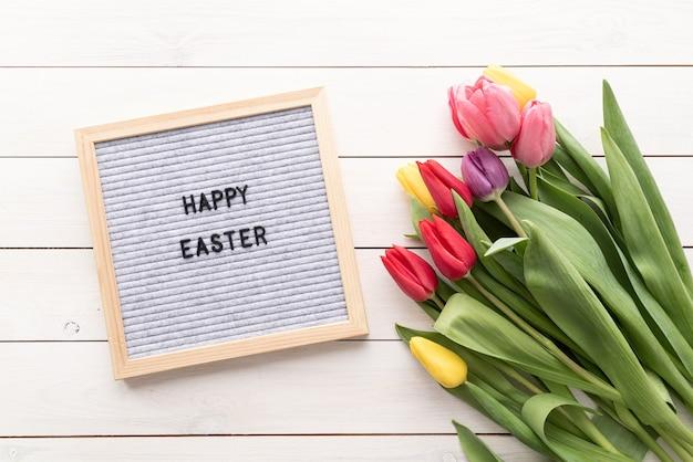 Conceito de primavera e páscoa. buquê de flores de tulipas coloridas e cartolina com as palavras feliz páscoa