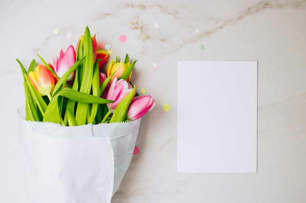 Conceito de primavera. tulipas cor-de-rosa e vermelhas com placa limpa branca para seu texto no fundo de mármore. copie o espaço, lay plana.