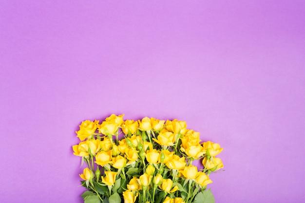 Conceito de primavera verão com flores de ovas amarelas na mesa roxa fundo vista superior espaço livre cópia espaço romântico