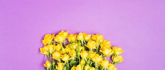 Conceito de primavera verão com flores rosas amarelas na mesa roxa fundo vista superior espaço livre cópia espaço romântico