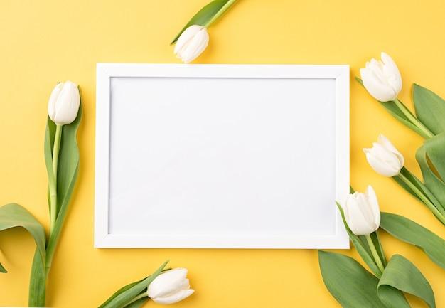 Conceito de primavera. vista superior de lindas tulipas brancas em fundo amarelo com uma moldura em branco.