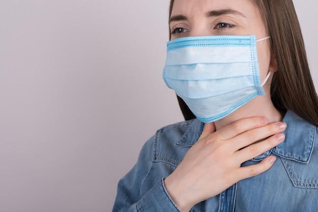 Conceito de primeiros sintomas do coronavírus. foto cortada em close de uma garota triste e infeliz, sofrendo de dor de garganta, tocando o pescoço com mão isolada superfície cinza com espaço de cópia vazio