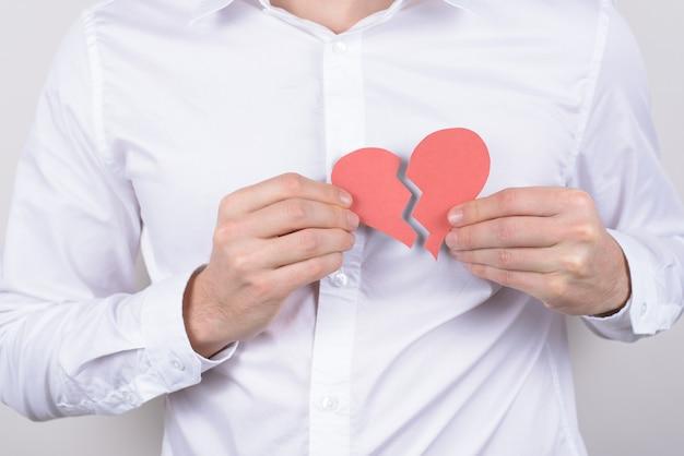 Conceito de problema de saúde cuidados insalubres de dor de dor no peito ataque de dor de coração cortado perto de um pequeno coração nas mãos isola a parede cinza
