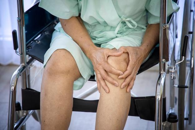 Conceito de problema de saúde; idosa com dor no joelho e esperando para encontrar o médico no hospital.