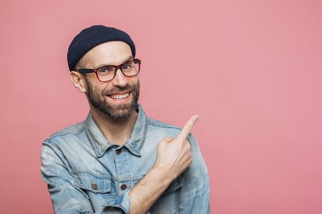 Conceito de propaganda. jovem barbudo alegre com expressão feliz usa óculos