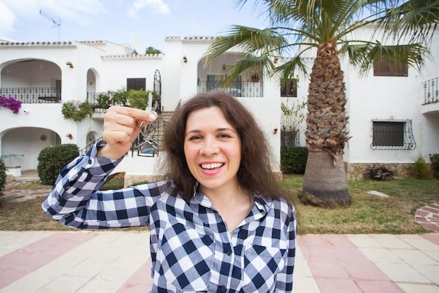 Conceito de propriedade, imobiliário, compra e aluguel - mulher com as chaves do lado de fora da nova casa