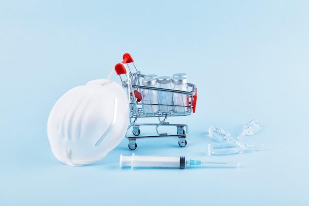 Conceito de proteção de coronavírus. mini carrinho de supermercado com medicamentos, seringa e escudo facial médico