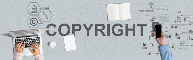 Conceito de proteção de direitos de propriedade intelectual. mãos em um laptop e segure um smartphone.