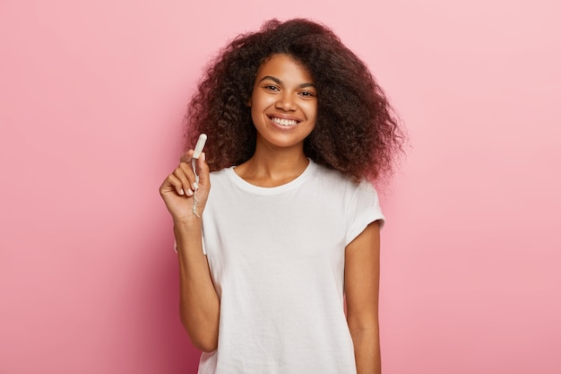 Conceito de proteção de higiene feminina. mulher alegre de pele escura segurando um tampão de algodão