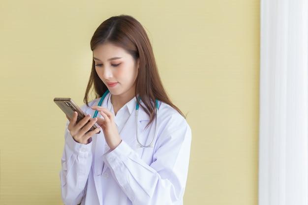 Conceito de proteção do coronavírus. médica asiática usando um telefone celular.