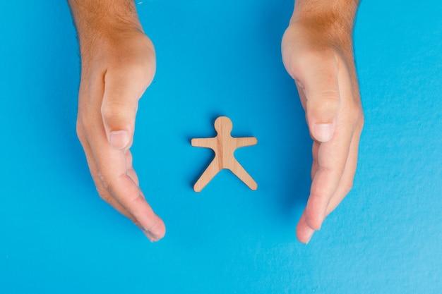 Conceito de proteção social na mesa azul plana leigos. mãos cuidando da figura humana de madeira.