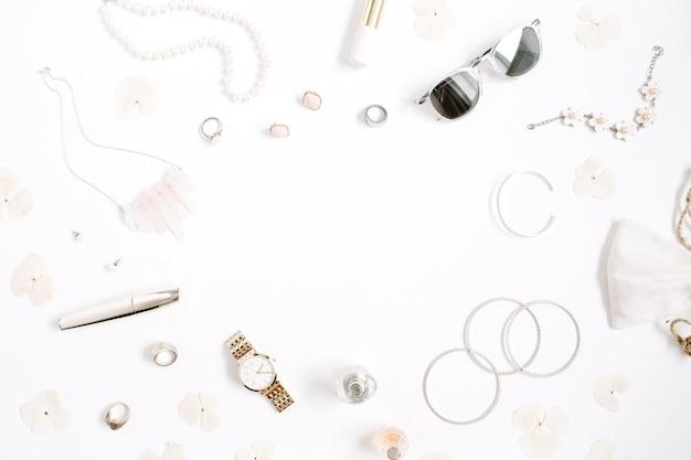 Conceito de quadro de blog de beleza. roupas e acessórios de mulher: relógios, óculos de sol, pulseira, colar, anéis, batom em fundo branco. plano leigo, vista superior, fundo feminino da moda na moda.