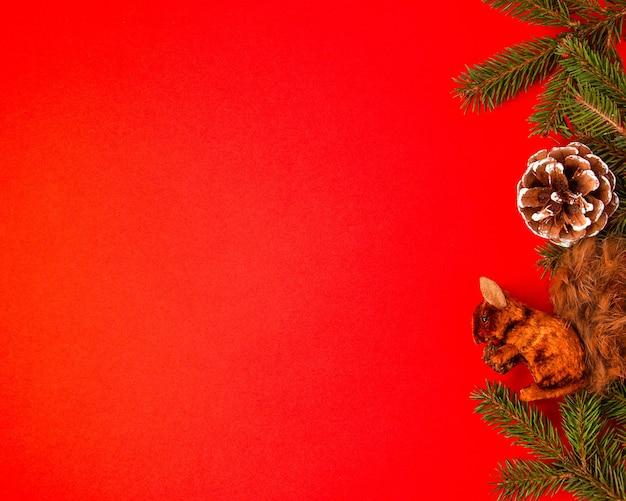 Conceito de quadro de natal e ano novo feito de galhos de árvore de abeto com pinha e esquilo em moldura de madeira plana vista de cima