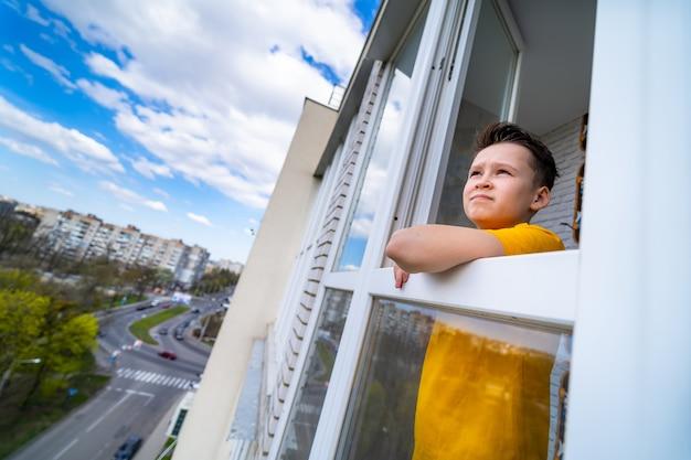 Conceito de quarentena de coronavírus. criança vestindo camiseta amarela, olhando pela janela. covid-19 - auto-isolamento. rapaz adolescente forçado a ficar em casa.