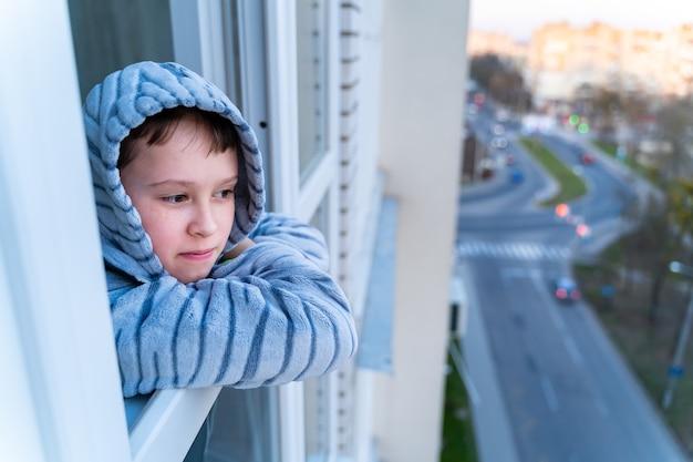 Conceito de quarentena de coronavírus. criança vestindo jaqueta com capuz durante o vírus da gripe, olhando pela janela. covid-19 - auto-isolamento. rapaz adolescente forçado a ficar em casa.