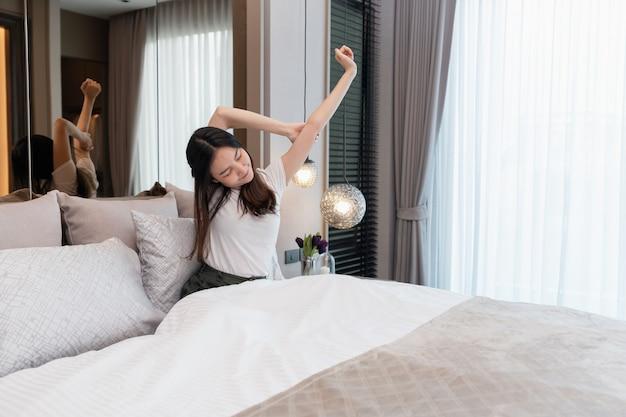 Conceito de quarto de uma menina bonita olhando dormindo esticando a parte superior do corpo depois de acordar de um sono profundo na noite passada.