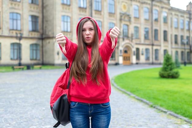Conceito de quebra de regras. foto de impressionante expressando sua indignação adolescente rebelde hippie com capuz mostrando o símbolo de dedos para baixo