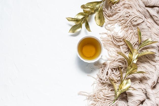 Conceito de queda. cobertor quente, ramos dourados decorativos e xícara de chá de ervas em fundo branco de concreto com espaço de cópia para seu projeto. composição do estilo hygge.