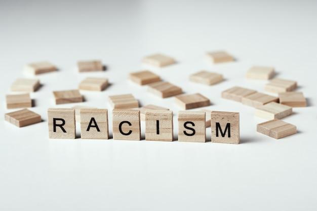 Conceito de racismo e incompreensão entre pessoas, preconceito e discriminação. bloco de madeira com palavra racismo no fundo branco