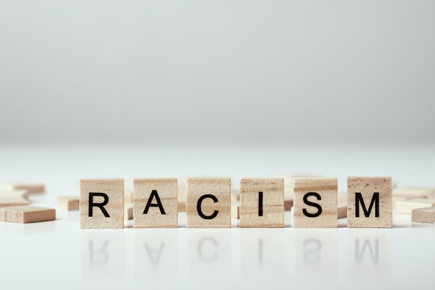 Conceito de racismo e incompreensão entre pessoas, preconceito e discriminação. bloco de madeira com palavra racismo
