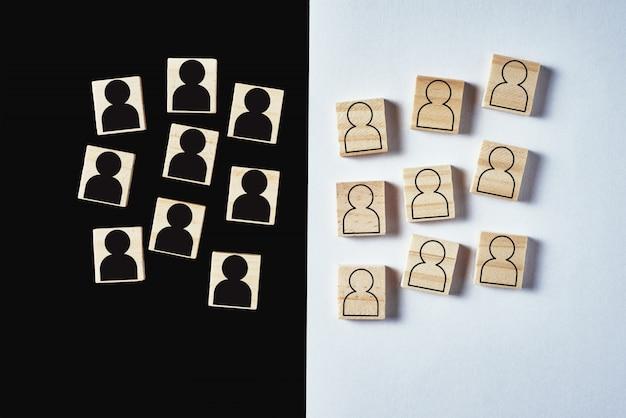 Conceito de racismo e incompreensão entre pessoas, preconceito e discriminação. bloco de madeira com um povo branco figuras e preto mans separados, vista superior