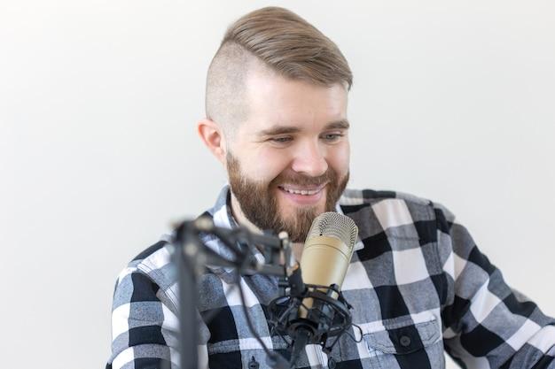 Conceito de rádio, dj e transmissão - retrato de jovem bonito com cabelo loiro apresentando programa ao vivo