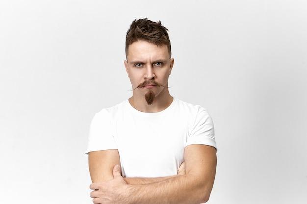 Conceito de raiva, mau humor e fúria. retrato de jovem bonito com bigode e barba por fazer, de braços cruzados sobre o peito e carrancudo, tentando conter sua raiva e reação negativa