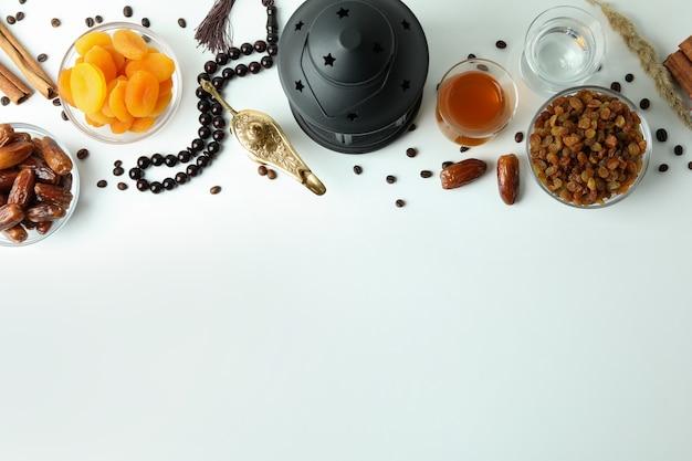 Conceito de ramadã com comida e acessórios na superfície branca, espaço para texto