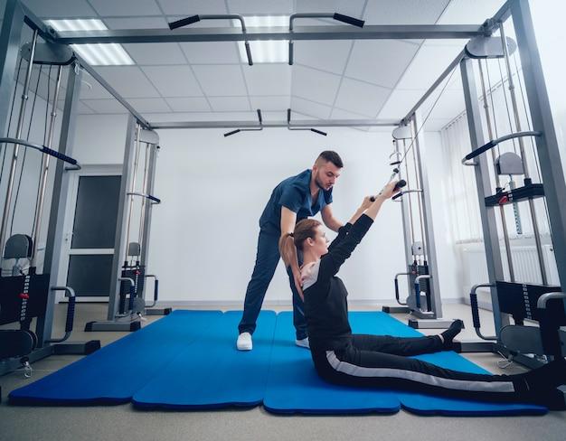 Conceito de reabilitação. mulher jovem e bonita fazendo exercícios na esteira, sob a supervisão do fisioterapeuta