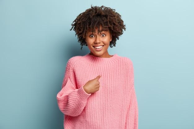 Conceito de reação humana. mulher de pele escura positiva tem cabelo crespo, aponta para si mesma, parece feliz