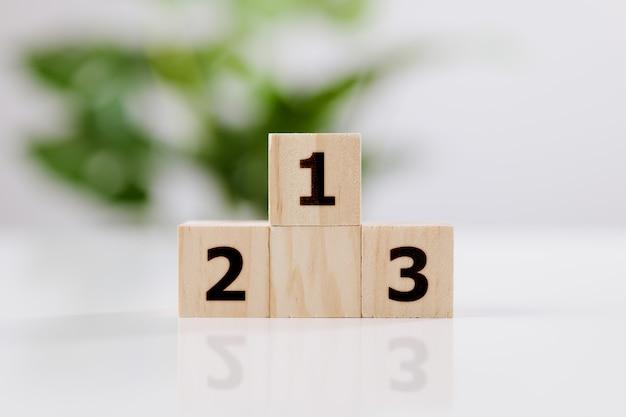 Conceito de realização. pódio de madeira em pé na mesa branca