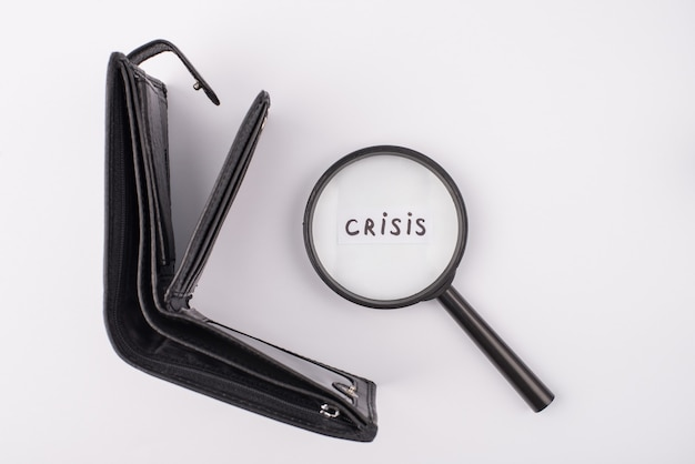 Conceito de recessão global 2020. no alto, acima, veja a foto da bolsa de couro preta aberta vazia e lupa com crise de palavras sobre fundo cinza
