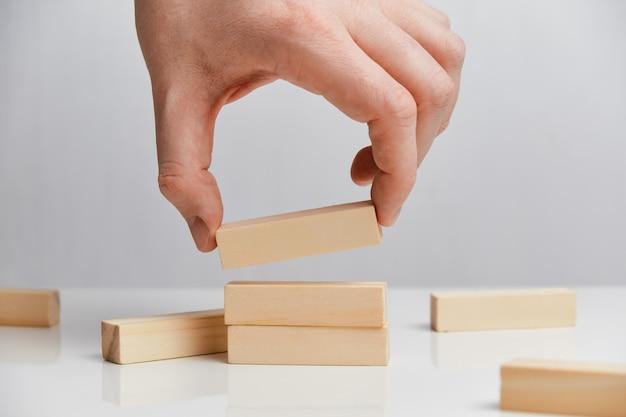 Conceito de reconstrução de um negócio após a falência. mão segura blocos de madeira em um espaço em branco.