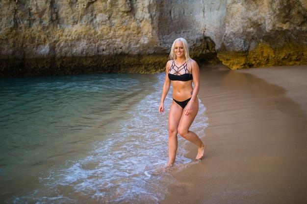 Conceito de recreação de verão. bela jovem mulher sexy com corpo magro treinado em biquíni maiô preto caminhando em uma praia à beira-mar