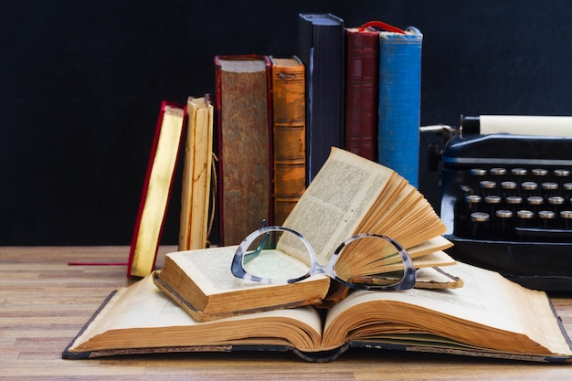 Conceito de redação e publicação de livros antigos, óculos e máquina de escrever