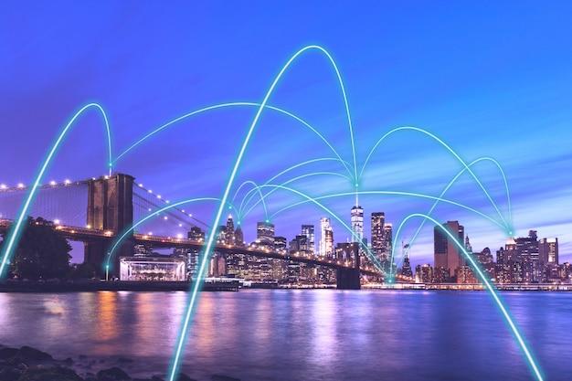Conceito de rede de comunicação da cidade inteligente 5g em nova york - downtown manhattan visão noturna com links abstratos que conectam edifícios, sem fio, visualização da internet das coisas