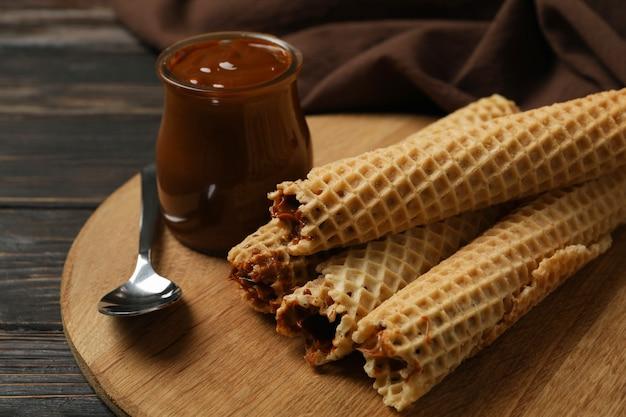 Conceito de refeição saborosa com rolinhos de wafer com leite condensado na madeira