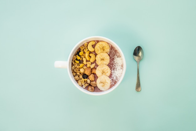 Conceito de refeição saudável: uma tigela de suco de frutas com nozes e fatias de banana. tigela de açaí com cereais, castanha de caju e avelãs