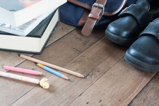Conceito de regresso à escola, sapatos da escola velha, saco e lápis no chão de madeira