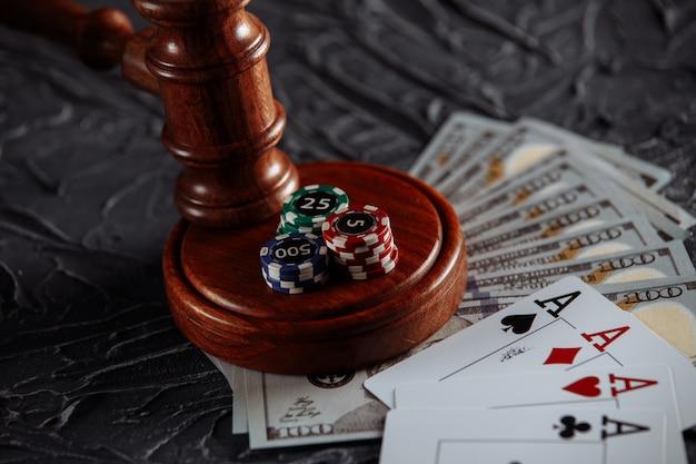 Conceito de regulamentação legal do jogo, martelo da justiça e dados no fundo de uma velha mesa cinza.
