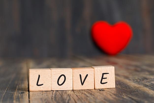 Conceito de relacionamento com coração vermelho, cubos de madeira na vista lateral para a mesa de madeira.