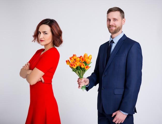 Conceito de relacionamento e amor - retrato de um homem com flores e uma garota triste e irritada sobre um fundo branco