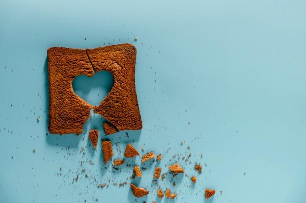 Conceito de relacionamento infeliz. flat lay de pão torrado queimado com um coração partido