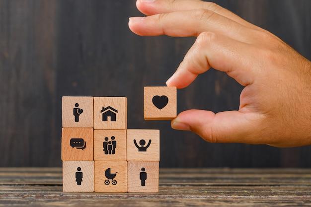 Conceito de relacionamento na vista lateral da mesa de madeira. mão segurando o cubo de madeira com o ícone de um coração.