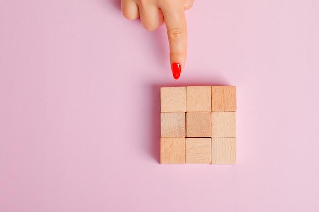 Conceito de relacionamento plano leigos. dedo mostrando blocos de brinquedo de madeira.
