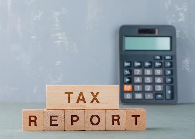 Conceito de relatório de imposto com blocos de madeira com palavras na vista lateral.
