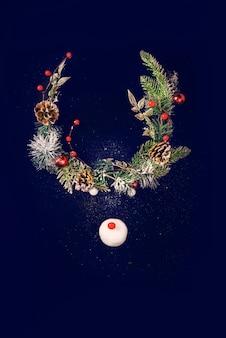 Conceito de rena de natal feito de abeto de natal, globo de neve na superfície preta cintilante. ideia mínima de férias de inverno. composição de vista superior plana leiga.