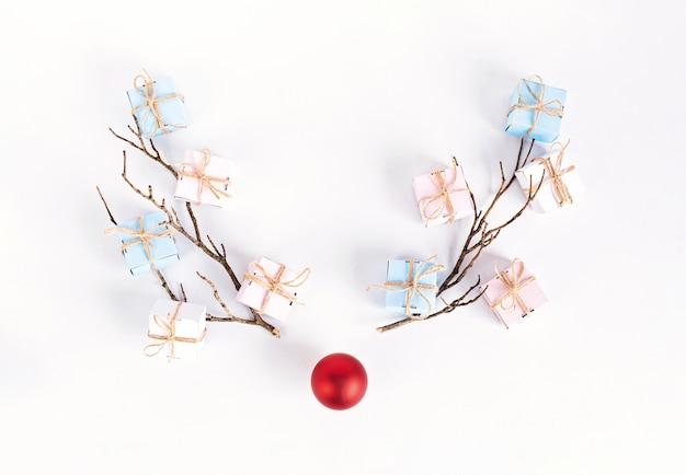 Conceito de rena de natal feito de galhos e bugigangas de natal. ideia sazonal de inverno minimalista. camada plana, composição de vista superior
